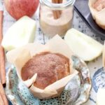 Apple & cinnamon muffin on a plate with apple chunks around it.