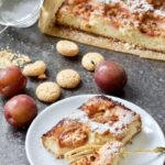 Plum and almond cake with plums and amaretti biscuits around it.