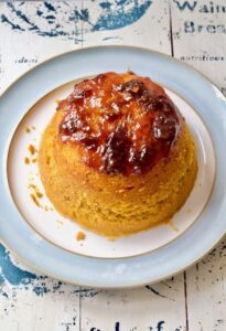 Whole pumpkin steamed sponge pudding on a plate.