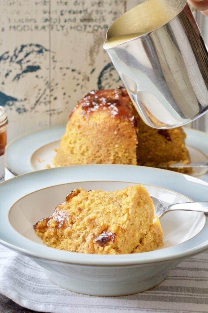 Bowl with slice of steamed pudding and jug with custard over it.