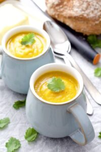 Close up of pumpkin soup with coriander leaf on top.