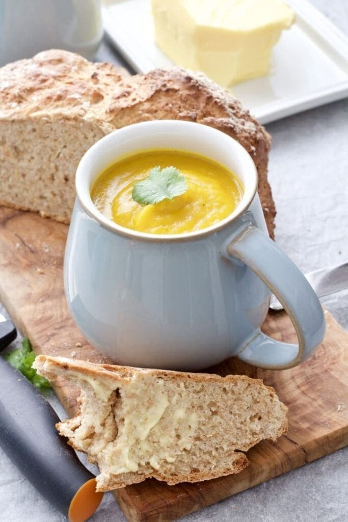 Soup in a mug on a board with slice of bread.