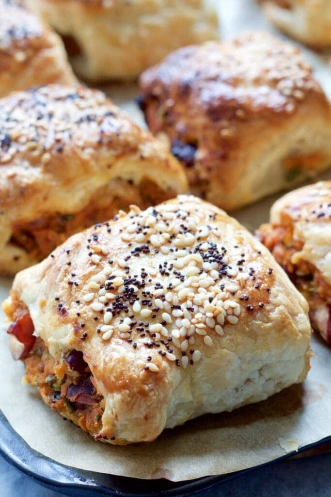 Veggie sausage rolls with sesame & poppy seeds on top.