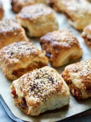 Close up of a veggie sausage roll on a baking tray.