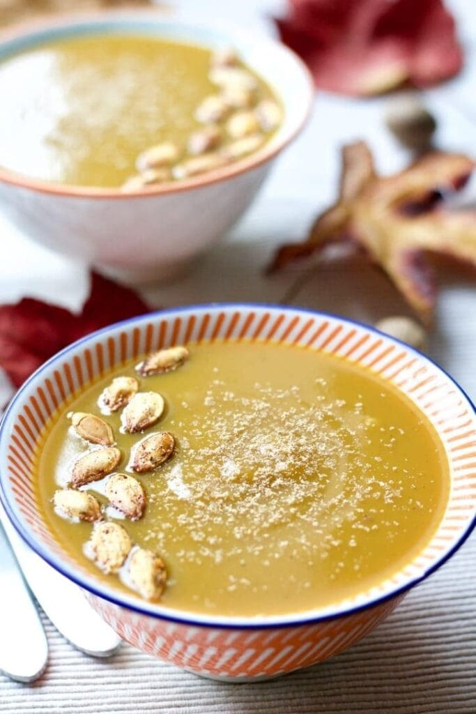 Close up of bowl with Butternut Squash & Chestnut Soup with pumpkin seeds on top.