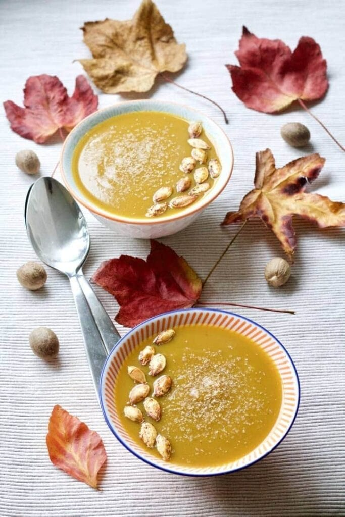 Two bowls of Butternut Squash & Chestnut Soup with leaves and nutmeg around them.