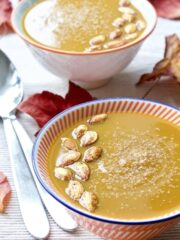 Butternut Squash & Chestnut Soup in a bowl with pumpkin seeds on top.