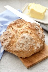 Soda bread loaf on a board with bread knife and butter.