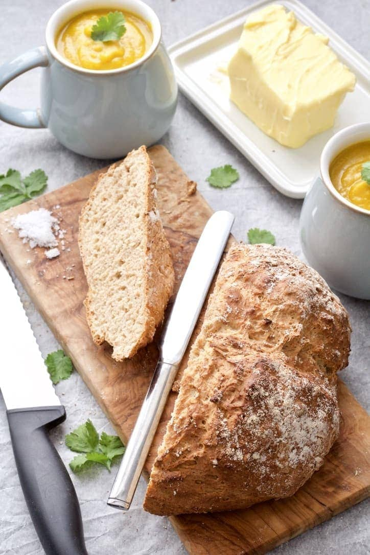 Bread loaf on cutting board with large slice cut off, soup & butter.