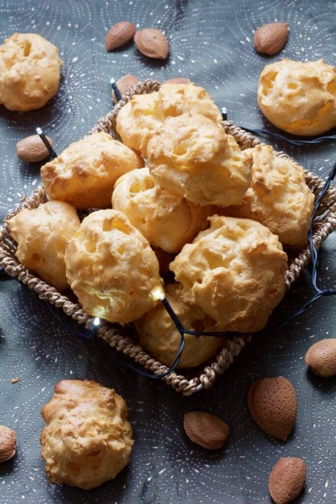 Gougeres in a basket with almonds and lights around.
