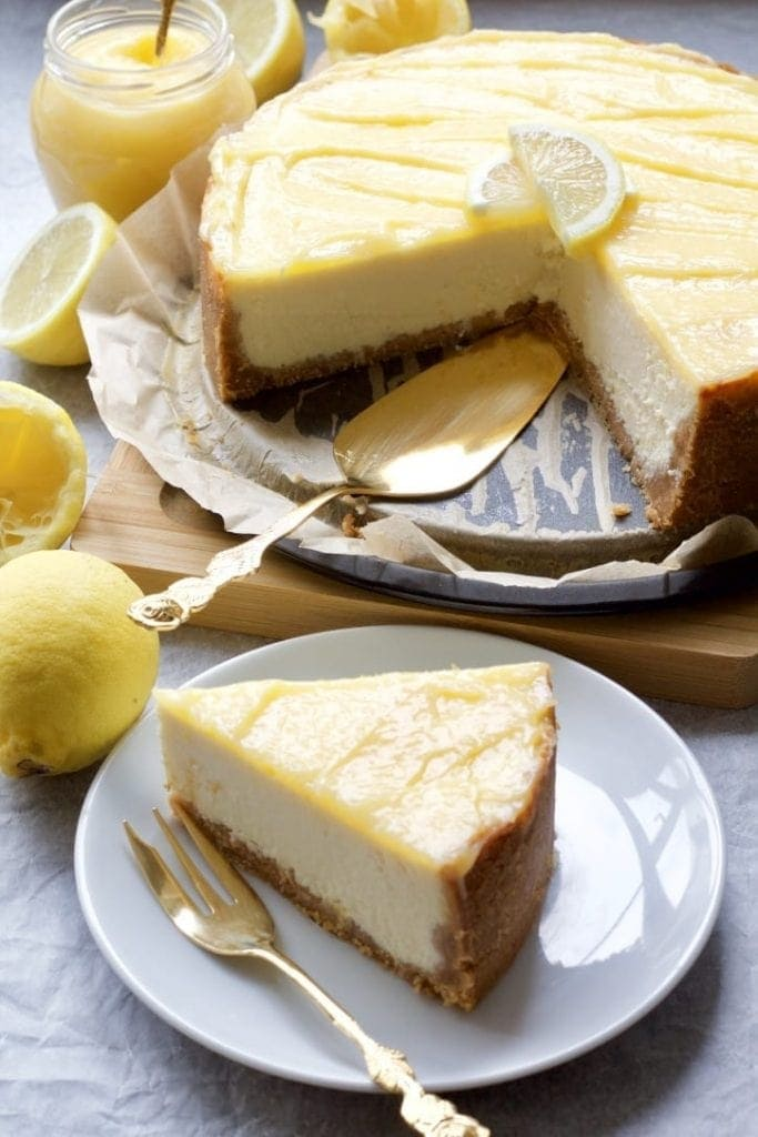 Cheesecake surrounded by lemons and jar of curd.
