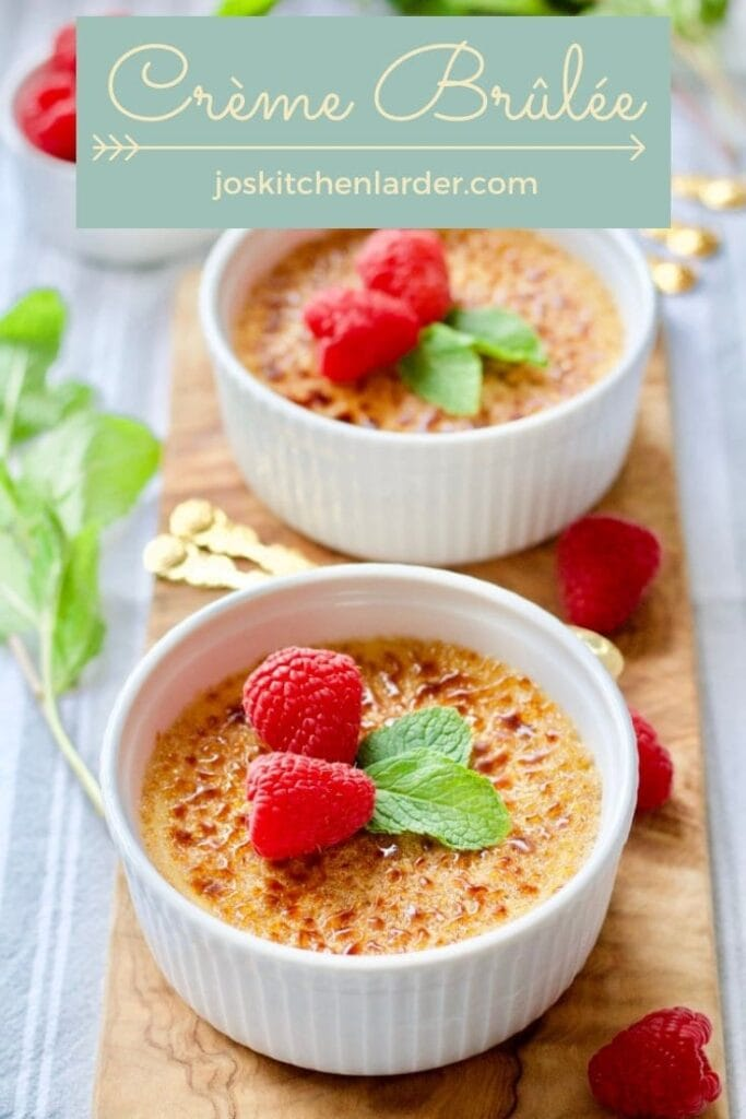 Crème Brûlée with mint and raspberries on a wooden board.
