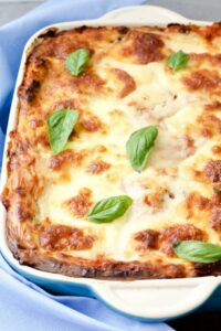 Lentil and Spinach Lasagne in a dish with basil leaves.