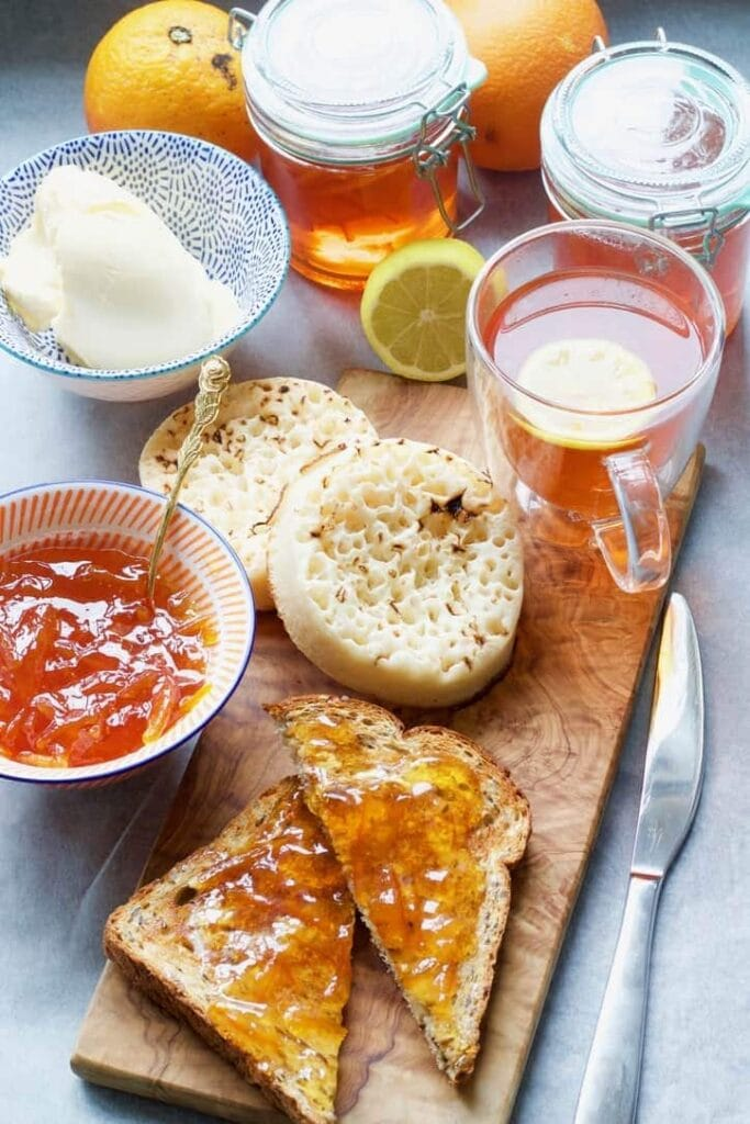 Breakfast set up with tea, toast, crumpets, butter and marmalade.