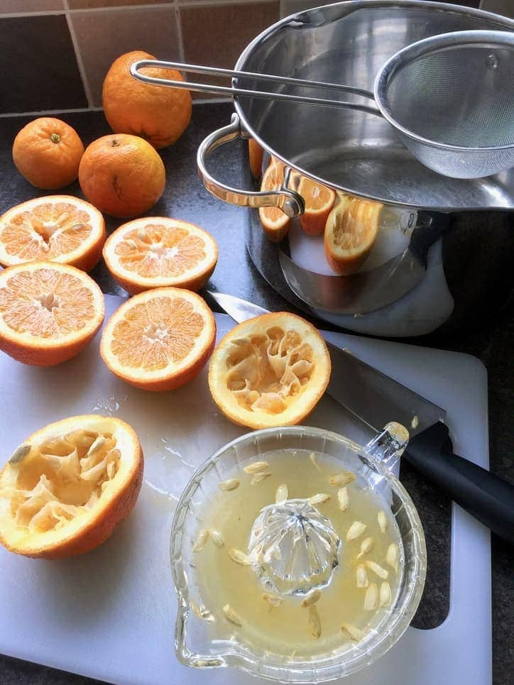 Oranges being juiced & large pot with a sieve.