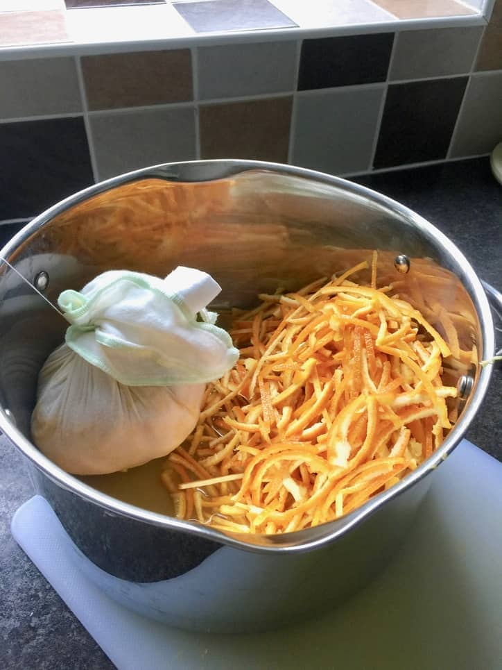 Pot with muslin bag and sliced orange rind.