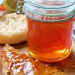 Jar of orange marmalade with piece of toast next to it.