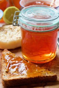 Jar of orange marmalade with piece of toast next to it.