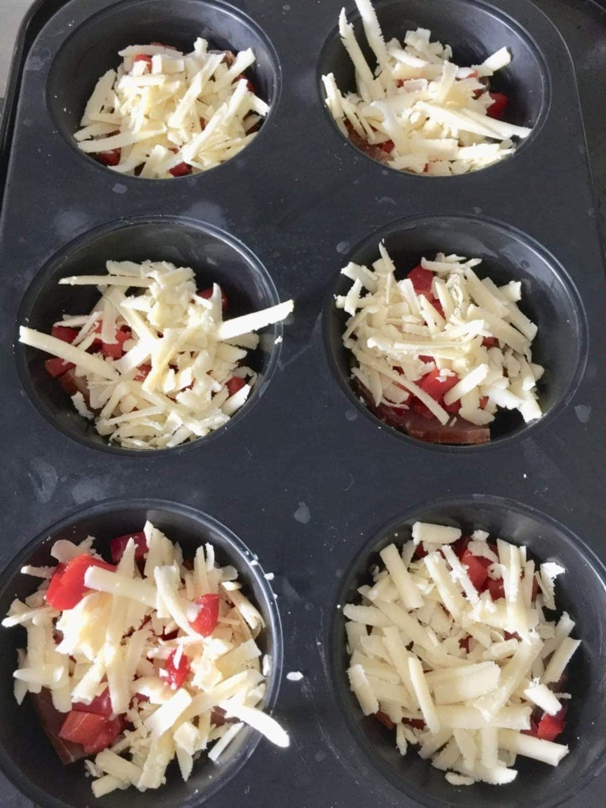 Pepper pieces & grated cheese in a muffin tin.