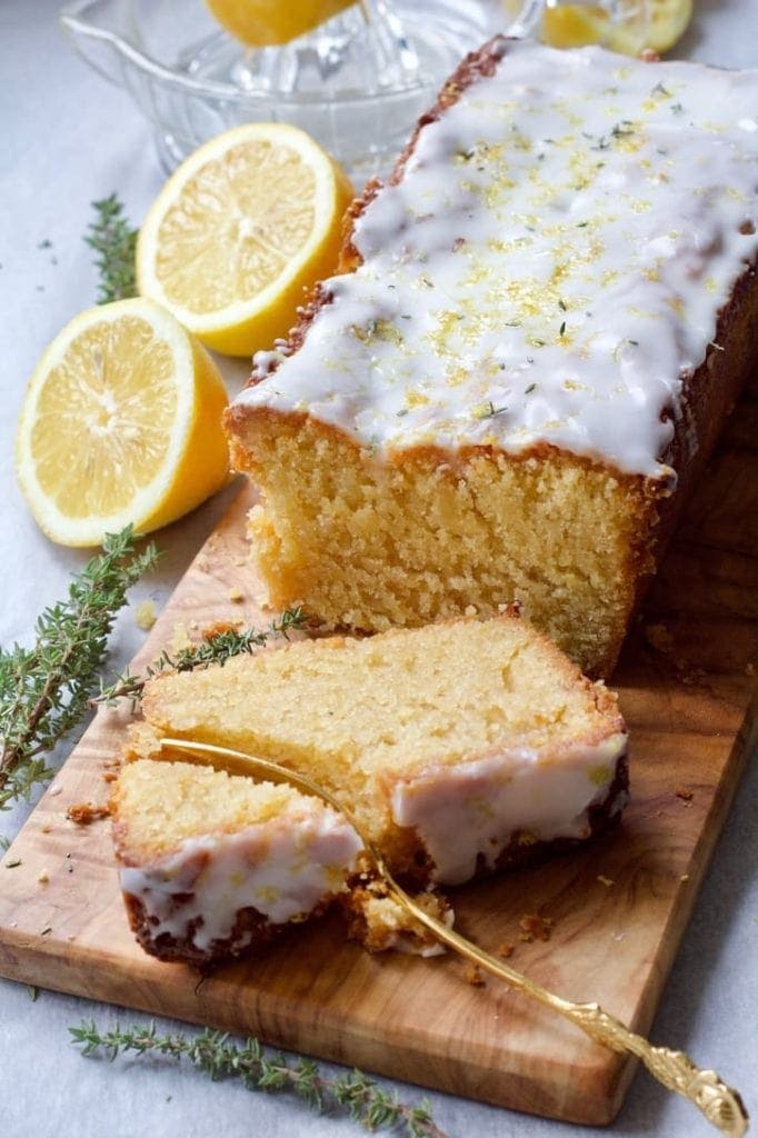 Vegan Lemon Drizzle Cake on a board with slice being cut with a fork.