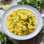 Bowlful of turmeric rice garnished with fresh coriander.