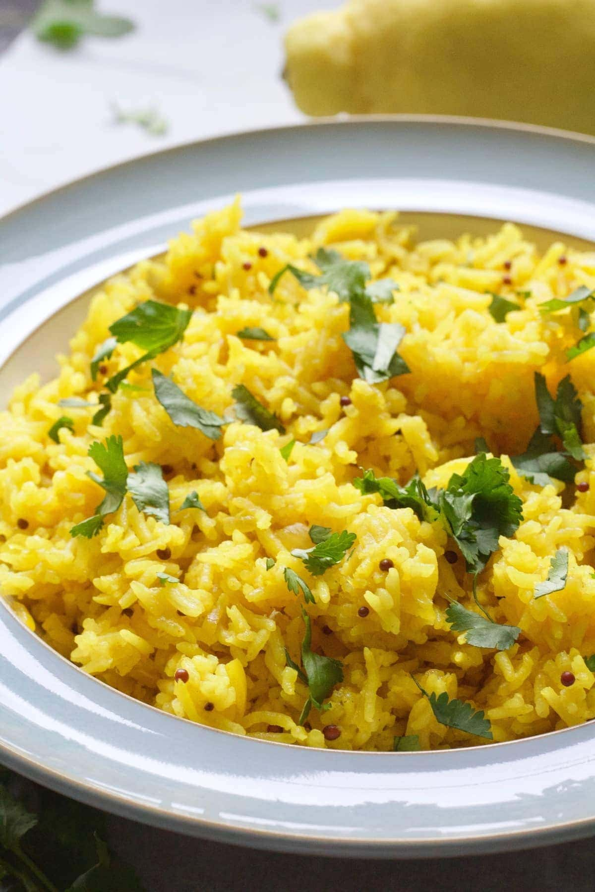 Yellow rice in a bowl with coriander garnish.