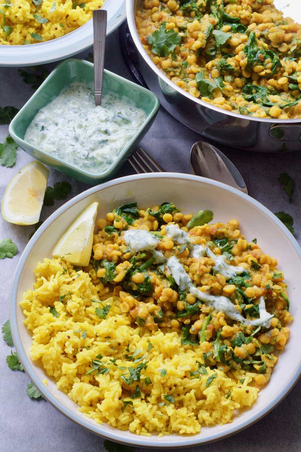Bowl of dhal with raita drizzle with rice & raita on the side.