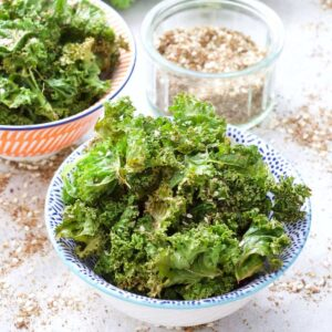 Kale crisps in a bowl with bowl of seasoning behind.