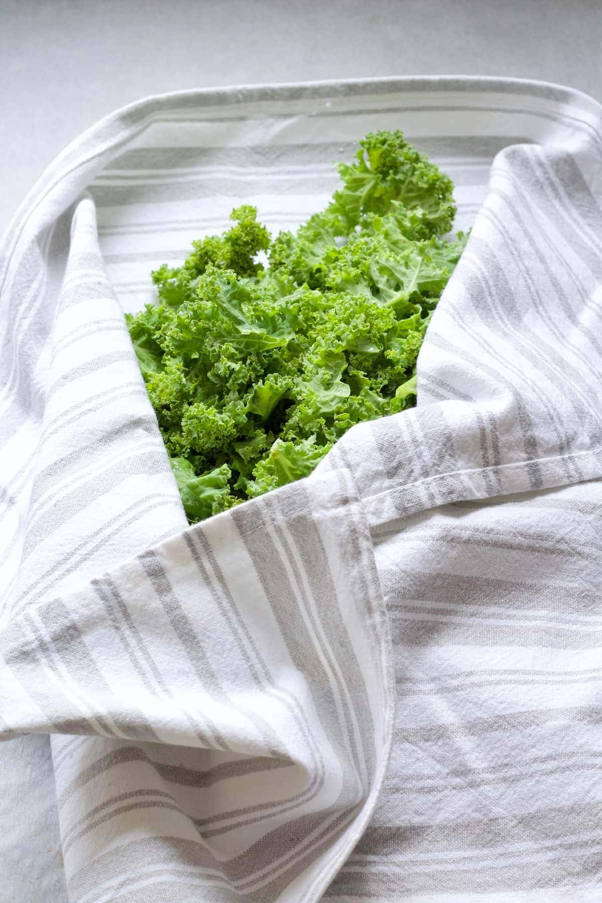 Washed greens wrapped in kitchen towel.