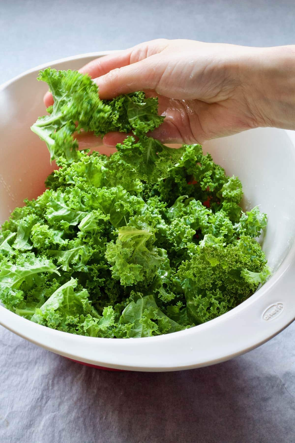 Massaging oil into kale leaves.