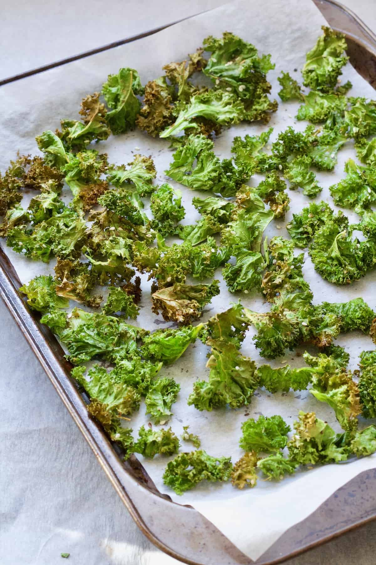 Baked kale crisps on a baking tray.