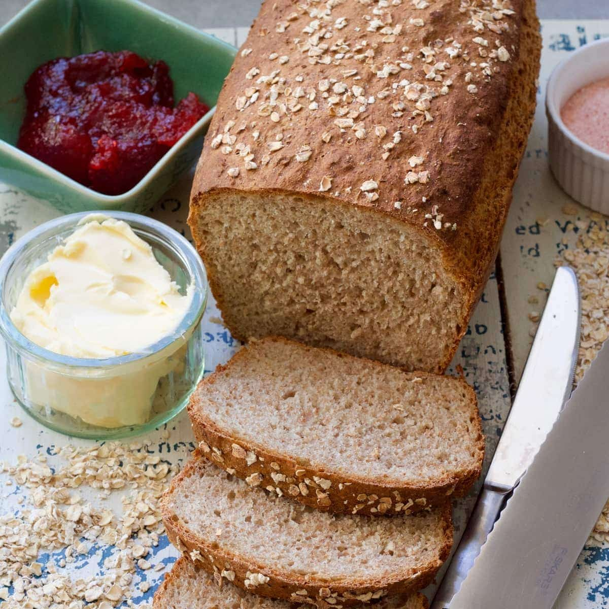 Bread with couple slices cut off, butter, jam & knives.