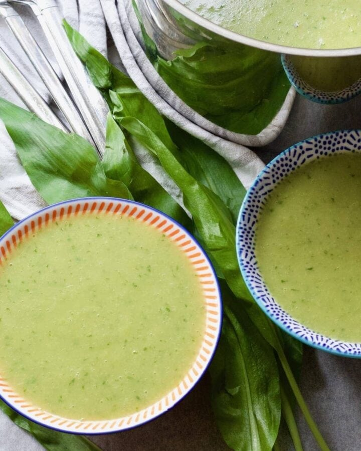 Wild garlic soup in bowls with leaves around.
