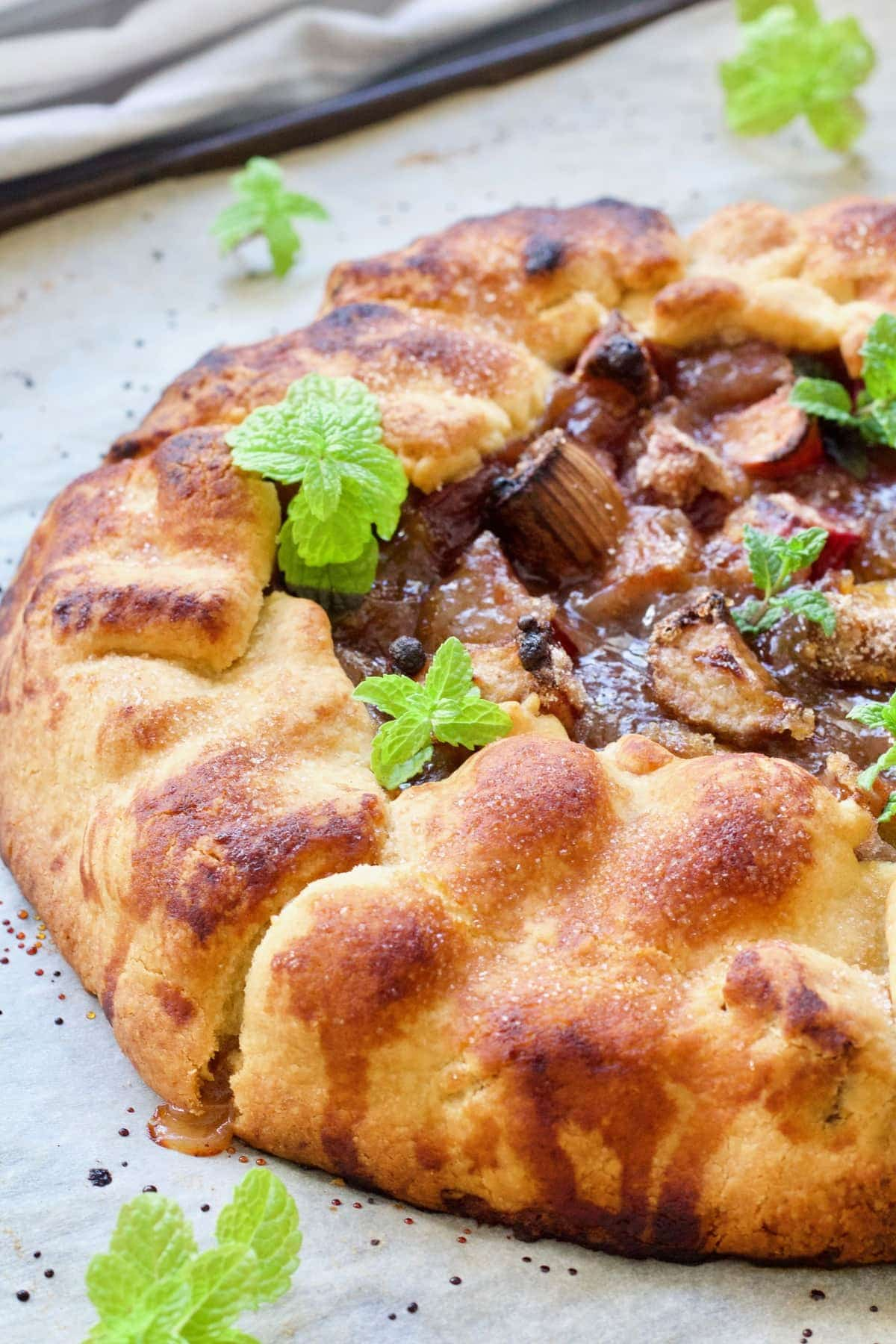 Close up of half of a rustic tart with mint garnish.