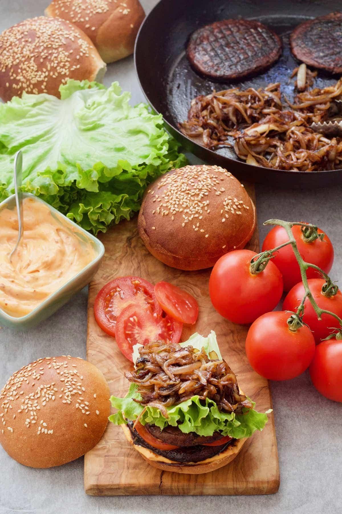 Portobello mushroom burger assembly with buns, tomatoes & lettuce.