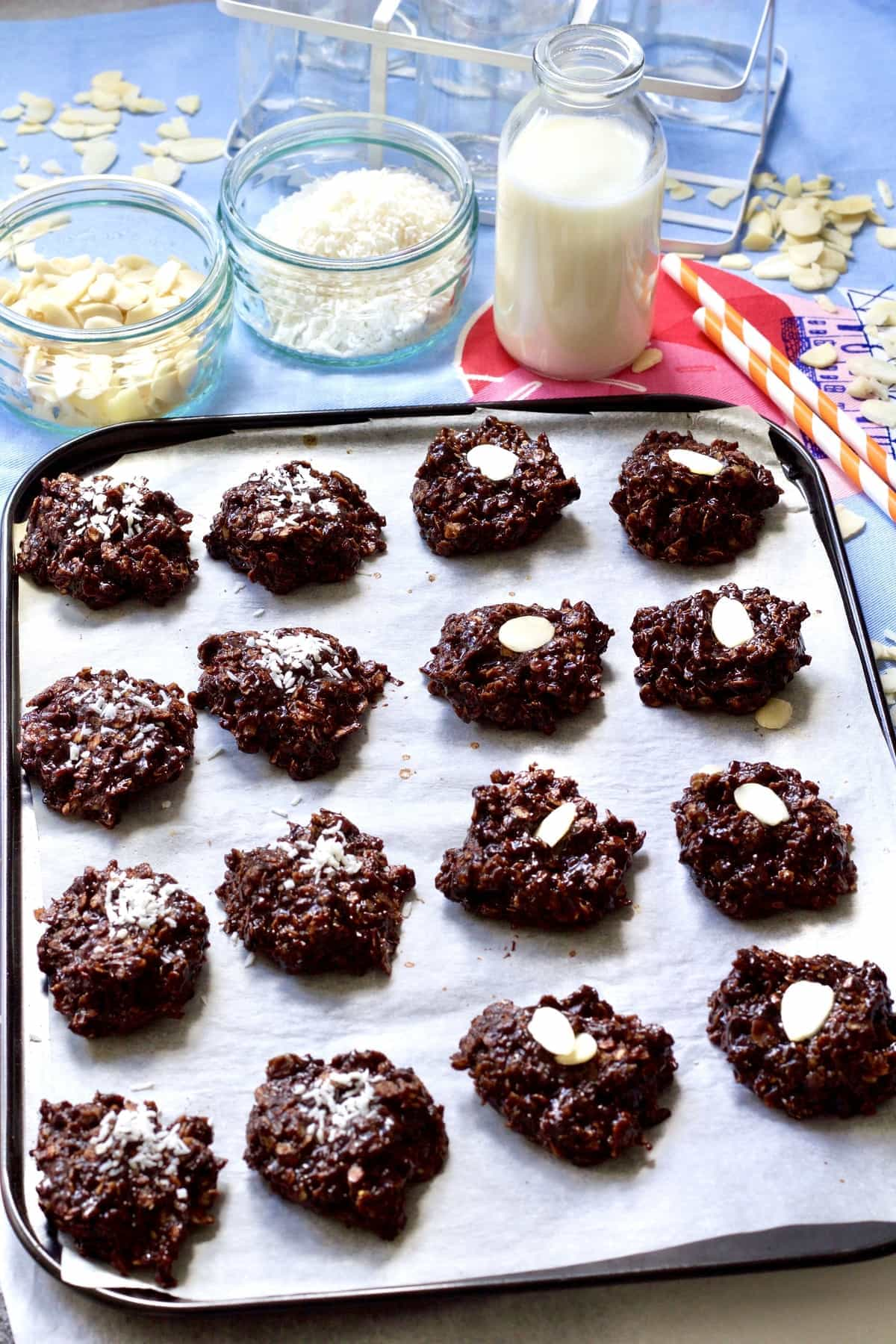 Cookies on a tray decorated with coconut and almonds.