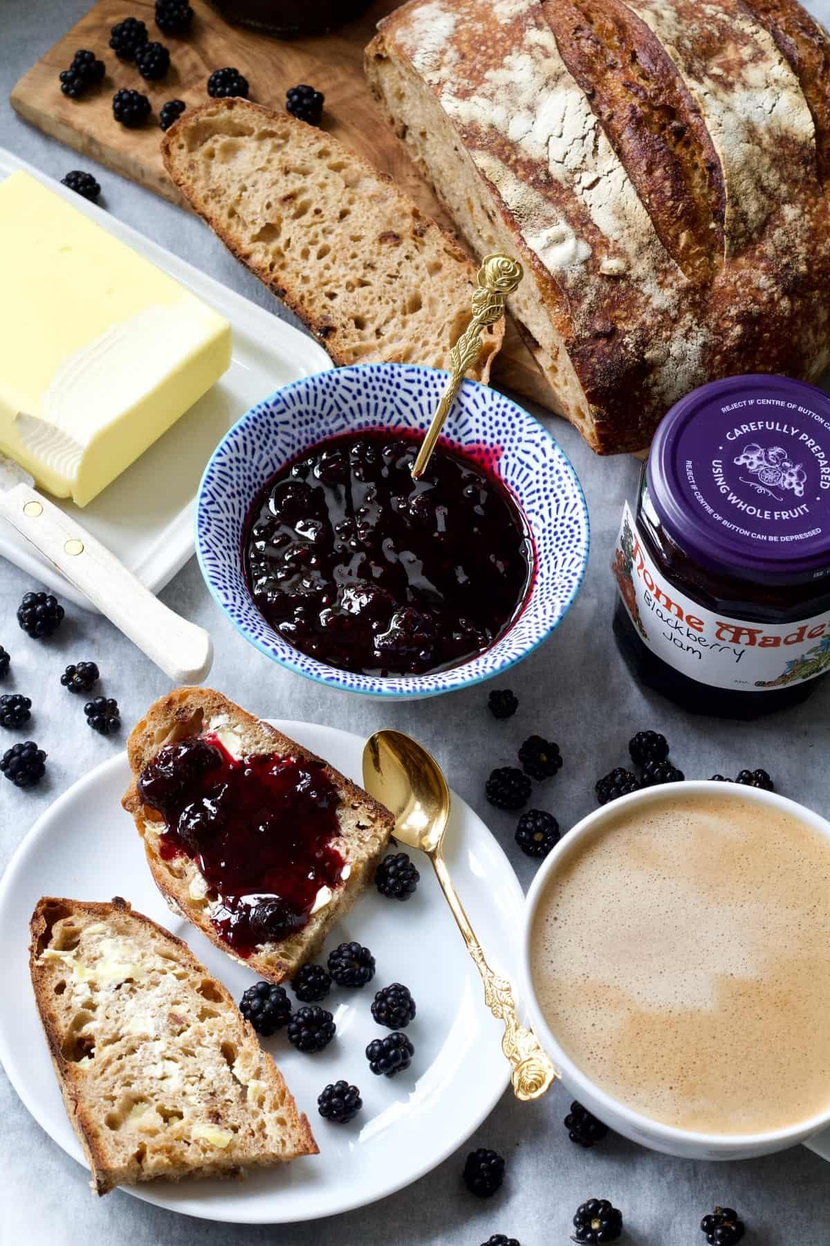 Breakfast spread with bread, blackberry jam, butter, coffee.