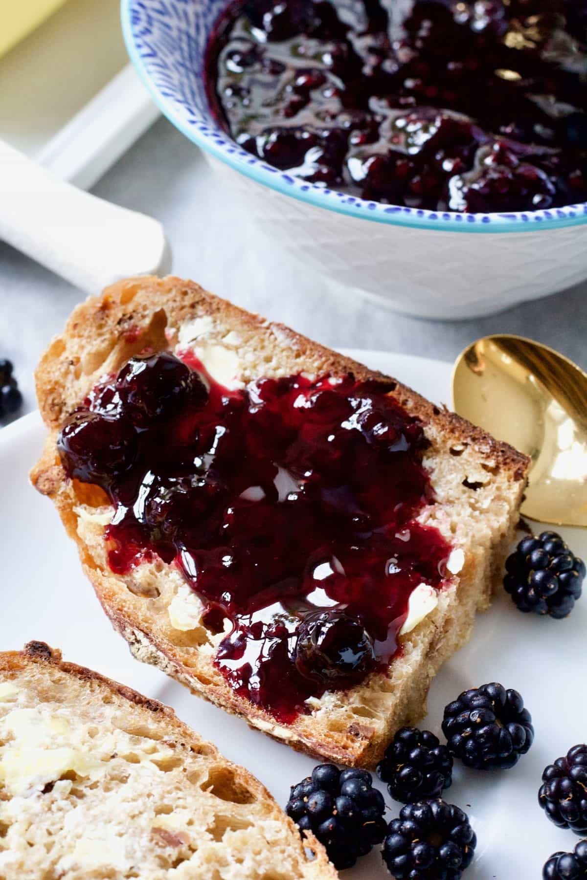 Half a slice of bread with blackberry jam on it.