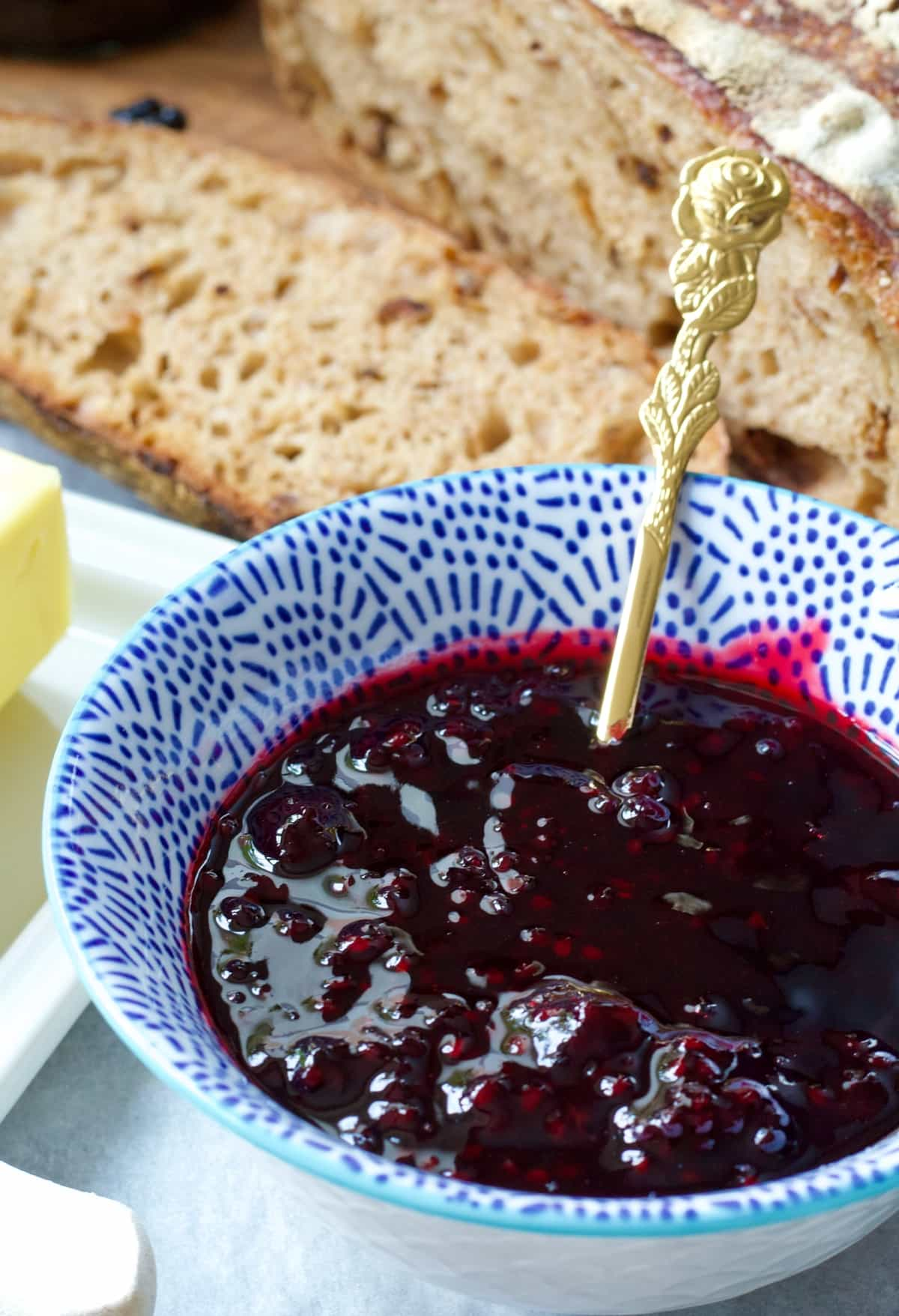 Bowl of blackberry jam with spoon in it.