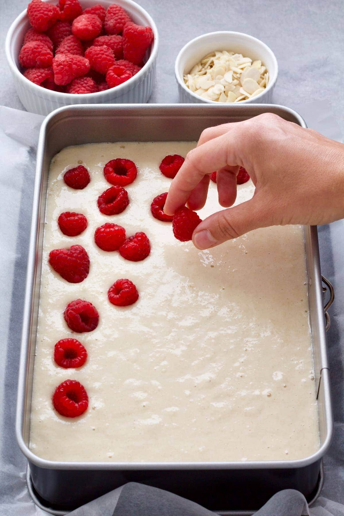 Hand putting raspberries on top of the cake batter.