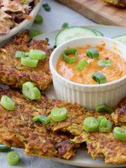 Close up of vegan vegetable fritters surrounding bowl with sauce.