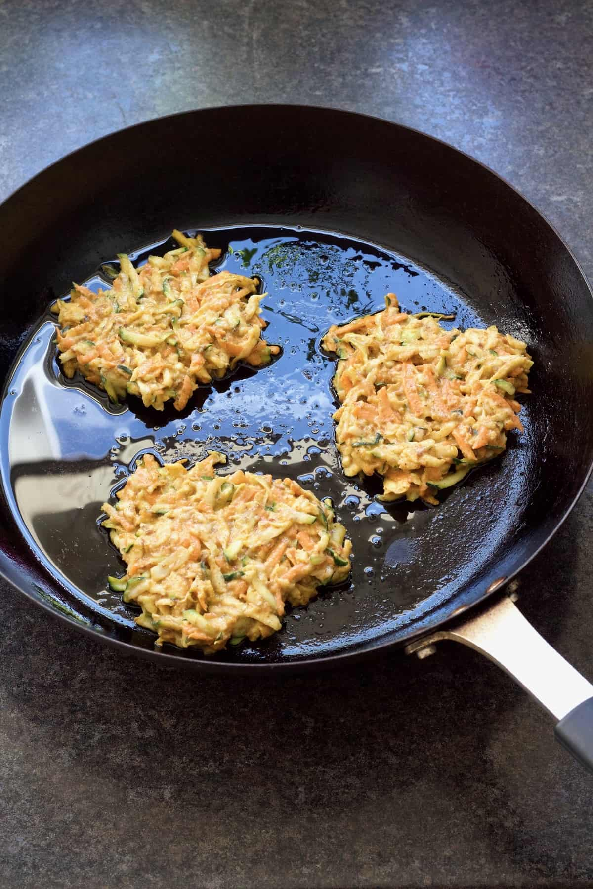 Three fritters in a frying pan.