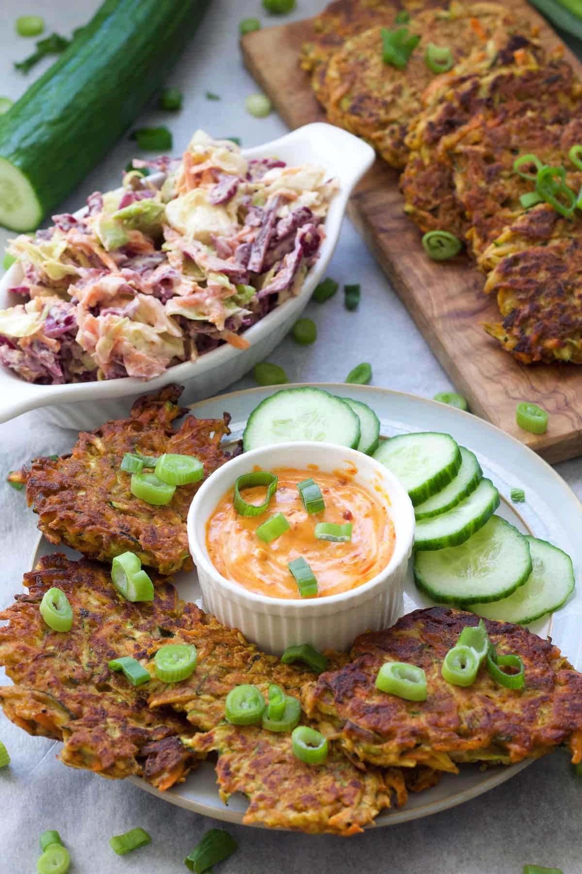 Vegan vegetable fritters on a plate with cucumber slices & sauce.