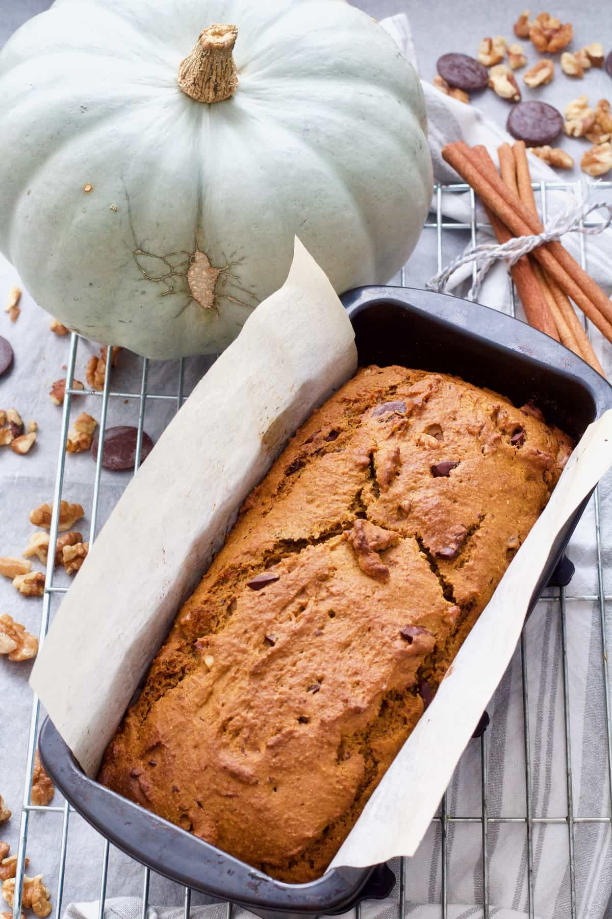 Pumpkin banana bread in a loaf tin on a rack.