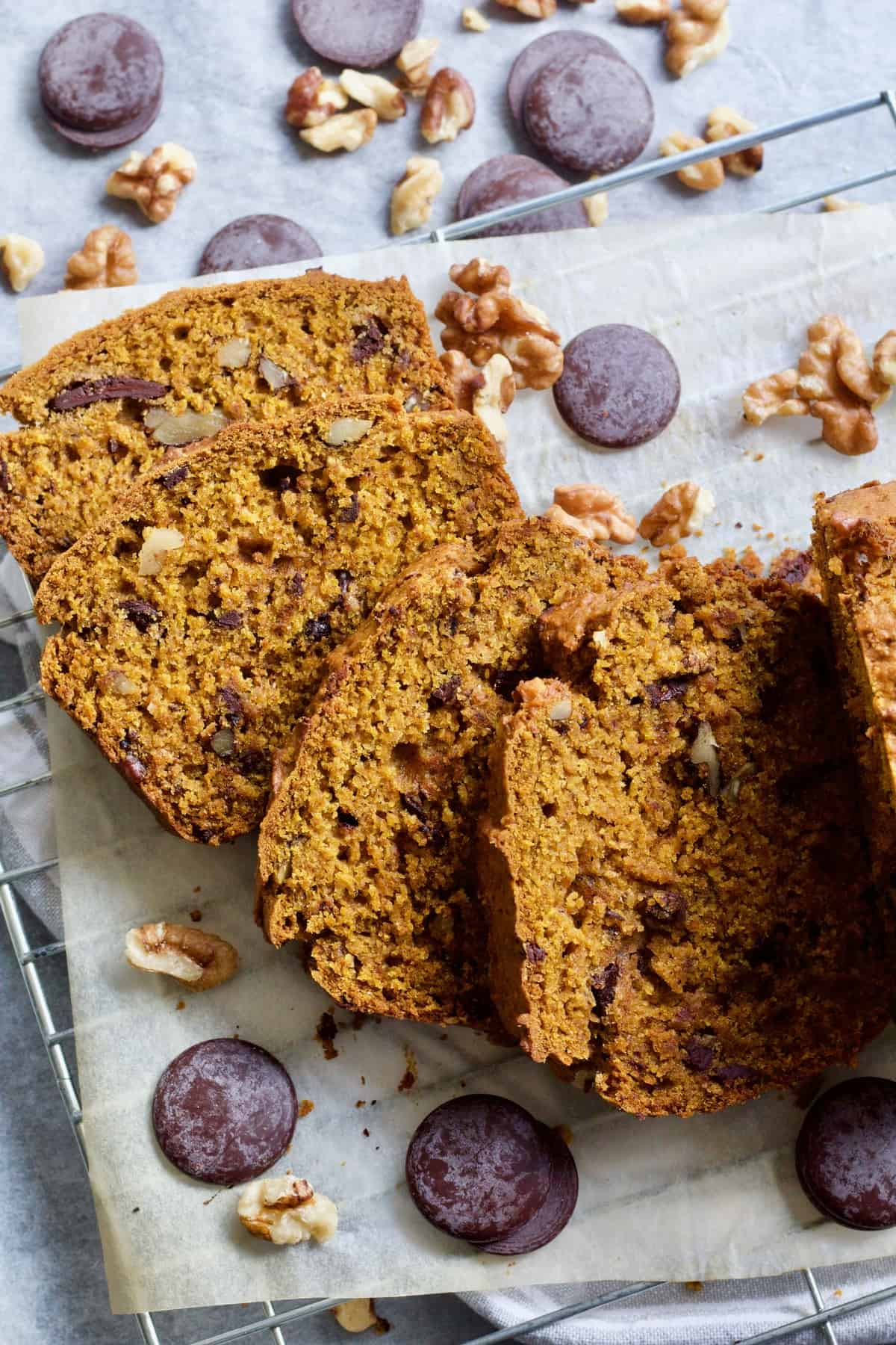 Four slices of pumpkin banana bread with chocolate & nuts around.