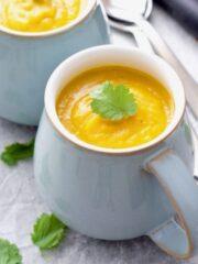 Mug filled with pumpkin soup garnished with coriander leaf.