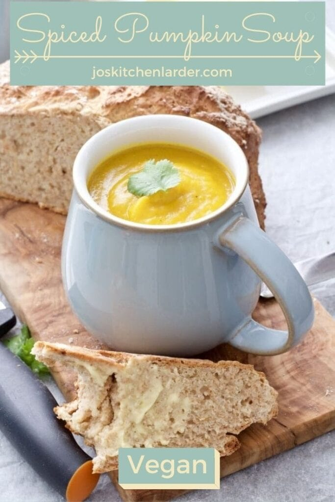 Mug with pumpkin soup and slice of buttered bread in front of it.