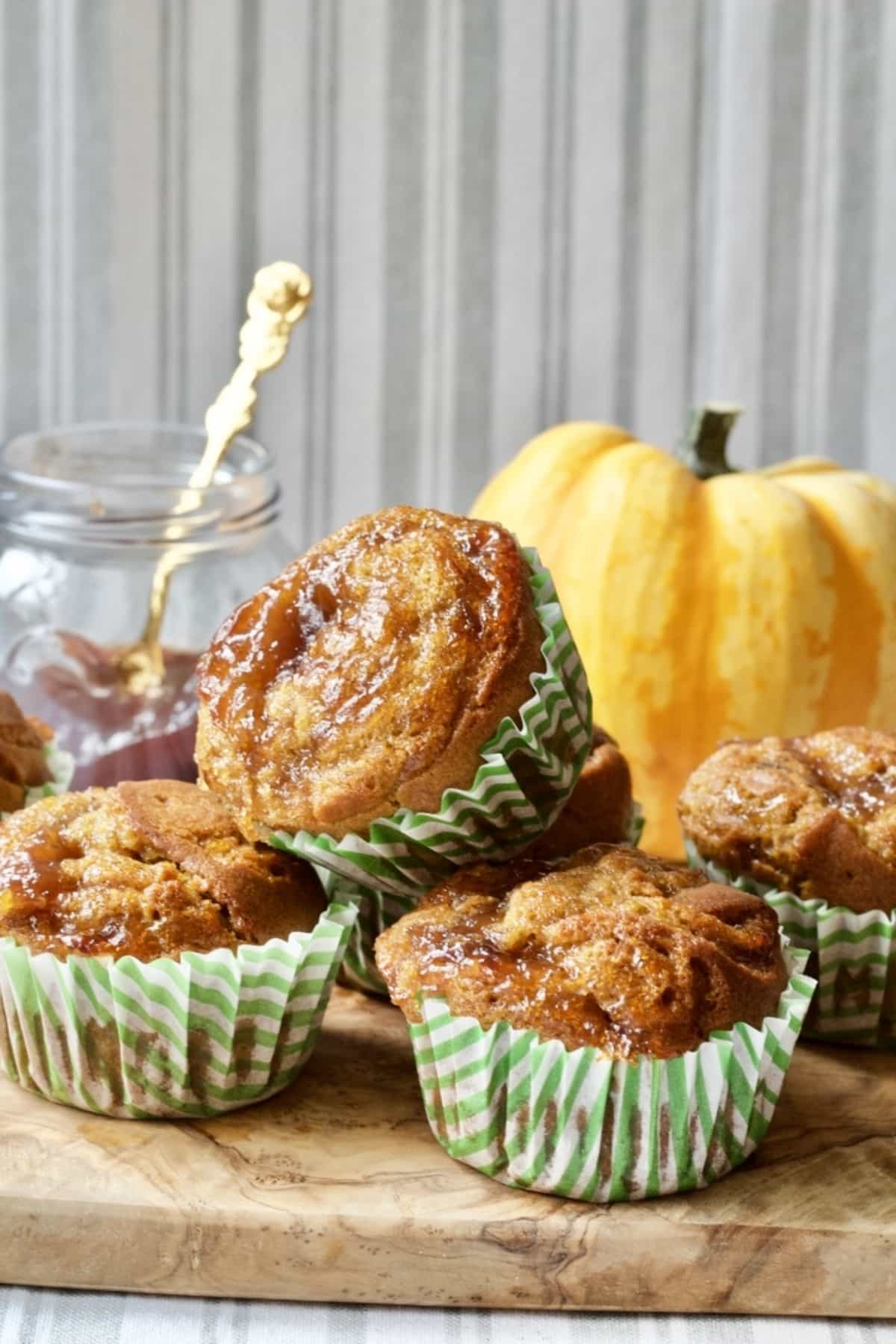 Vagen pumpkin muffins with pumpkin & jar of jam behind.
