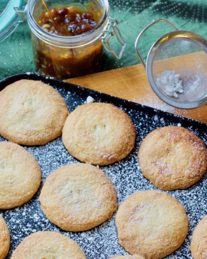 Mince pies in a tray, sieve and mincemeat jar.