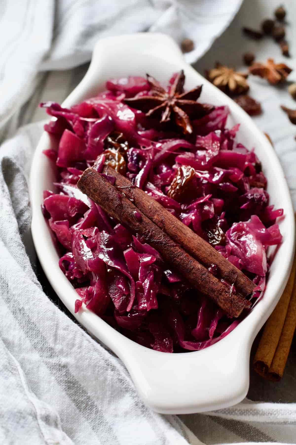 Red cabbage in a white oval dish with cinnamon stick.